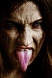 Mujer siniestra asustadiza malvada con la lengüeta hacia fuera imagen de archivo libre de regalías