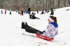 Mujer sledding abajo de la colina nevosa 3 Foto de archivo libre de regalías