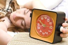 Mujer snoozing un reloj de alarma rojo Fotos de archivo