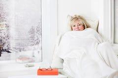 Mujer snuggling bajo una manta foto de archivo