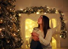 Mujer soñadora cerca del árbol de navidad con las luces que adorna Imagen de archivo
