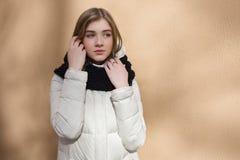 Mujer soñadora hermosa joven de la estación fría en la capa blanca que presenta contra la pared texturizada con el concepto liger Foto de archivo libre de regalías