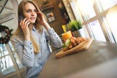 Mujer soñadora que habla en el teléfono sobre él con su amigo que gandulea en un café de moda cómodo Foto de archivo