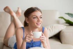 Mujer soñadora que se relaja en el sofá cómodo, disfrutando de la taza de coffe Fotos de archivo