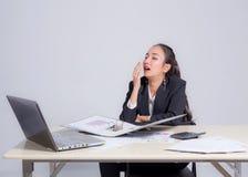 Mujer soñolienta cansada que bosteza - trabajando en el trabajo excesivo y el sueño del escritorio de oficina imagenes de archivo