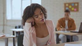 Mujer soñolienta cansada que duerme en una conferencia la muchacha de piel morena está bostezando Grupo de estudiantes en el fond almacen de video