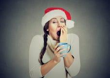 Mujer soñolienta de la Navidad que bosteza sosteniendo la taza de bebida caliente imagen de archivo
