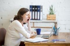 Mujer soñolienta del trabajador joven que bosteza fotos de archivo