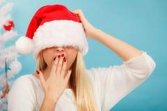 Mujer soñolienta en el sombrero de Papá Noel Imagenes de archivo
