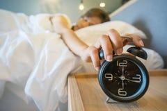 Mujer soñolienta en la cama que cambia del despertador imágenes de archivo libres de regalías