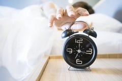 Mujer soñolienta en la cama que cambia del despertador foto de archivo