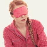 Mujer soñolienta que lleva la banda rosada del ojo imagen de archivo