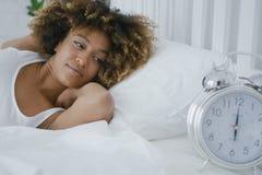 Mujer soñolienta que mira la alarma Imagen de archivo libre de regalías