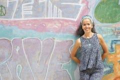 Mujer sobre inclinarse sonriente 50 en luz del sol de la pared de la pintada Fotos de archivo libres de regalías