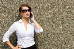 Mujer sofisticada con las gafas de sol usando el teléfono elegante móvil Foto de archivo