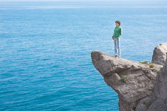 Mujer sola delgada joven que se coloca en el borde del acantilado a de la montaña Fotos de archivo libres de regalías
