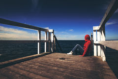 Mujer sola en camisa roja en el borde del embarcadero Imágenes de archivo libres de regalías