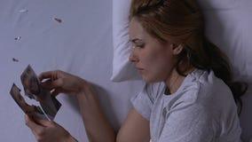 Mujer sola en la cama que lleva a cabo pedazos de foto rasgada y que llora, traición del marido almacen de video