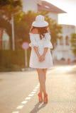 Mujer sola en un sombrero en un camino vacío Fotografía de archivo