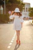 Mujer sola en un sombrero en un camino vacío Fotos de archivo