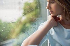 Mujer sola hermosa que se sienta delante de ventana Fotografía de archivo libre de regalías