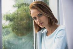Mujer sola que descansa mientras que llueve Fotos de archivo