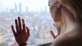 Mujer sola que mira a través de ventana a la opinión de la ciudad almacen de metraje de vídeo