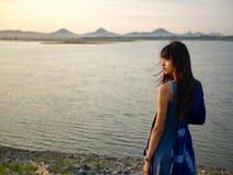 Mujer sola que se coloca cerca del río y de la puesta del sol imagenes de archivo