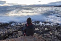 Mujer sola que se sienta al lado del mar Imagen de archivo libre de regalías