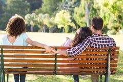 Mujer sola que se sienta con los pares en parque Imagenes de archivo
