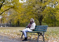 Mujer sola que se sienta en banco Imagenes de archivo