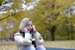 Mujer sola que se sienta en banco Fotos de archivo