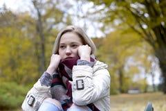 Mujer sola que se sienta en banco Fotografía de archivo libre de regalías