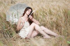 Mujer sola que se sienta en campo de trigo Fotos de archivo libres de regalías