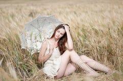 Mujer sola que se sienta en campo de trigo Foto de archivo libre de regalías