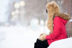 Mujer sola que se sienta en el banco al aire libre en invierno Imagen de archivo libre de regalías