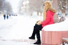 Mujer sola que se sienta en el banco en parque en invierno Imágenes de archivo libres de regalías