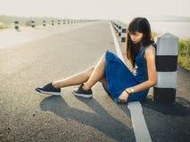 Mujer sola que se sienta en el camino fotografía de archivo libre de regalías