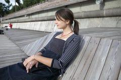 Mujer sola que se sienta por el río imagen de archivo