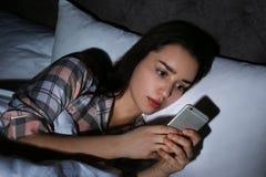 Mujer sola triste que usa el teléfono elegante fotografía de archivo libre de regalías