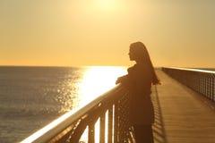 Mujer solamente que comtempla el océano en la puesta del sol foto de archivo