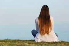 Mujer solamente que mira el cielo el sentarse en la hierba Fotografía de archivo