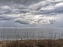 Mujer solitaria en las nubes de observación de la playa sobre el océano Fotos de archivo libres de regalías