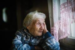 Mujer solitaria mayor en la casa que se sienta en la tabla que mira hacia fuera la ventana fotos de archivo
