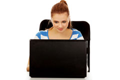 Mujer sonriente adolescente que usa el ordenador portátil Fotografía de archivo