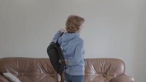 Mujer sonriente adulta hermosa que toma una mochila del sofá que va en un viaje metrajes