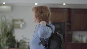 Mujer sonriente adulta hermosa que toma una mochila que va en un viaje almacen de video