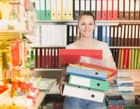 Mujer sonriente adulta que se coloca con las carpetas Imágenes de archivo libres de regalías