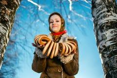 Mujer sonriente agradable en panecillos rusos nacionales de la demostración de la habitación en el día de invierno soleado entre  Imágenes de archivo libres de regalías