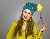 Mujer sonriente aislada en el fondo gris que sostiene la torre Eiffel Imágenes de archivo libres de regalías